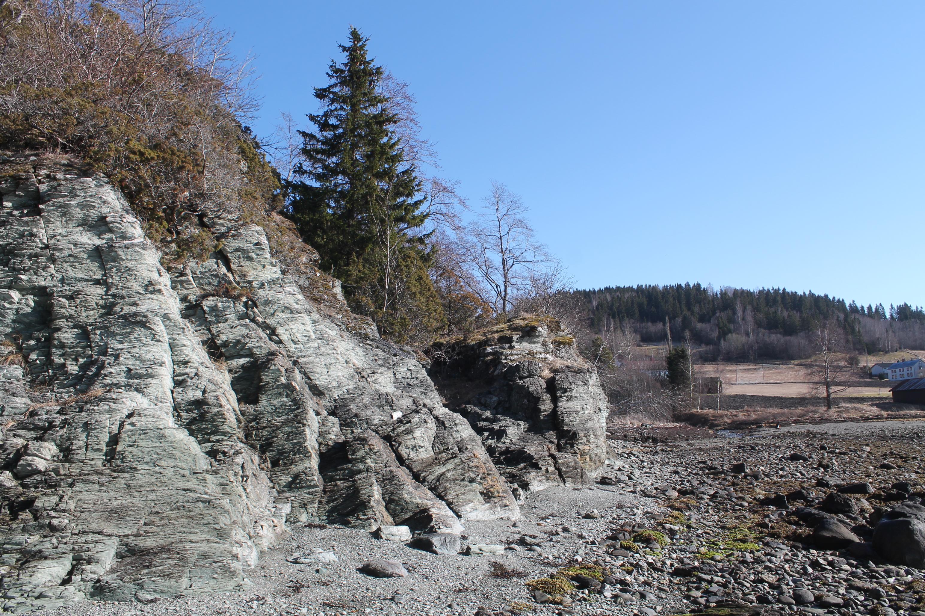 8. Nils forteller at et sted i dette berget bygget han, sammen med Johannes og nabogutta, en koselig hytte med vedovn. I bakgrunnen Sjøbygda med gården Forr